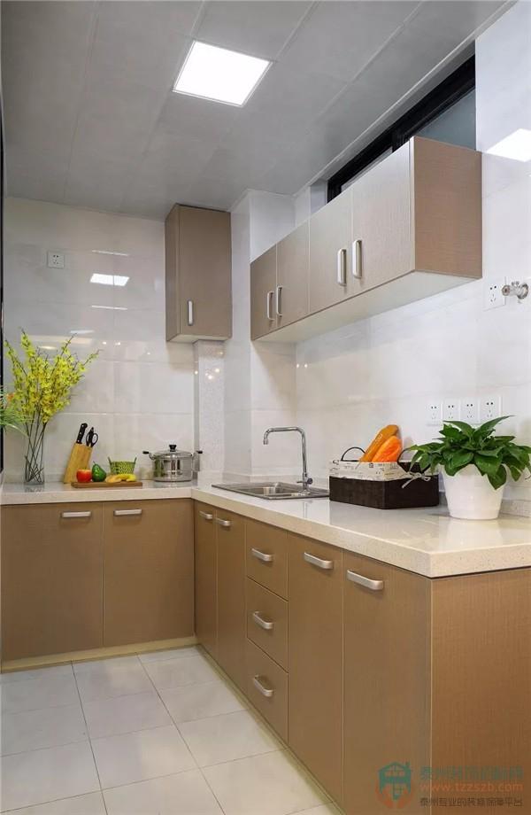 客厅另一角是l型厨房,整体设计以白色为主色调,收纳柜则用暗金色和米图片